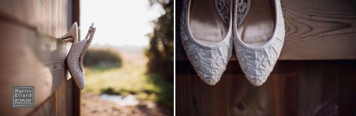 wedding dress hanging in a sunlit barn gower wedding